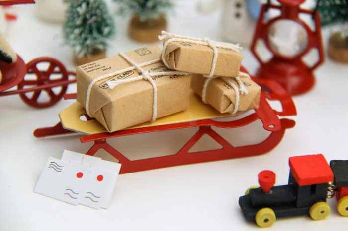 red sleigh figurine, with three small presents, wrapped in beige paper, and tied with white string, three tiny letters, and other toys, advent calendar filling
