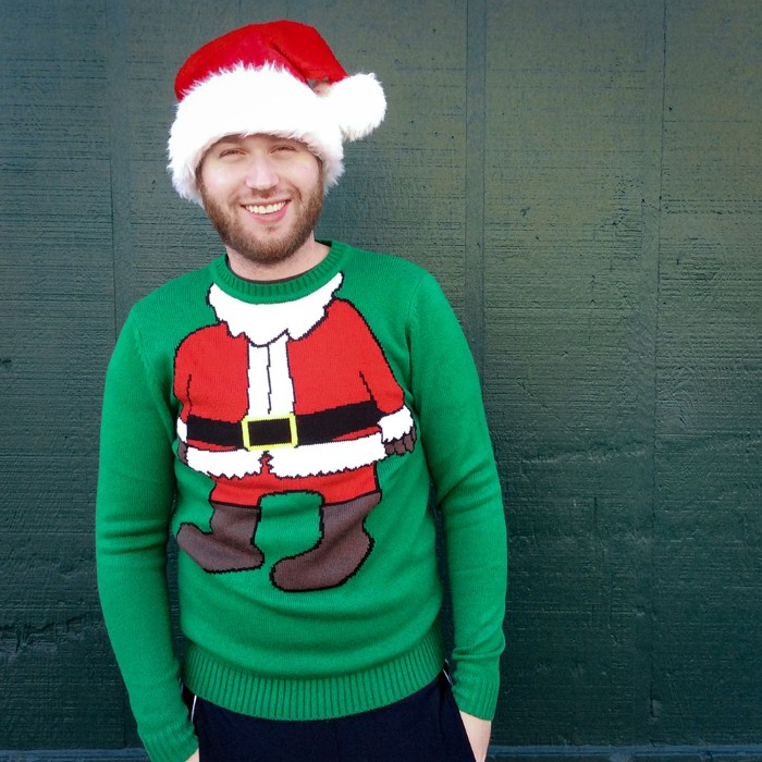 santa's body drawn on a green jumper, worn by a smiling young man, with a short beard, ugly sweater ideas, combined with a red and white santa hat