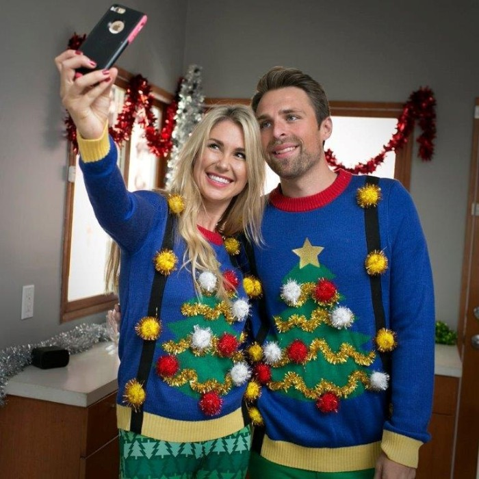 identical blue jumpers, with christmas trees, decorated with gold garlands, and white and red pom poms, worn by a smiling couple, posing for a selfie