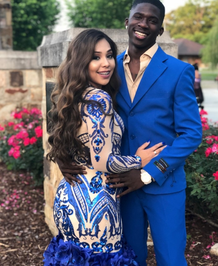 formal and semi formal wedding attire, couple dressed in complementary outfits, she is in a pale nude beige dress, with silky electric blue embroidery and frills, and he is wearing an electric blue suit, with a light beige shirt