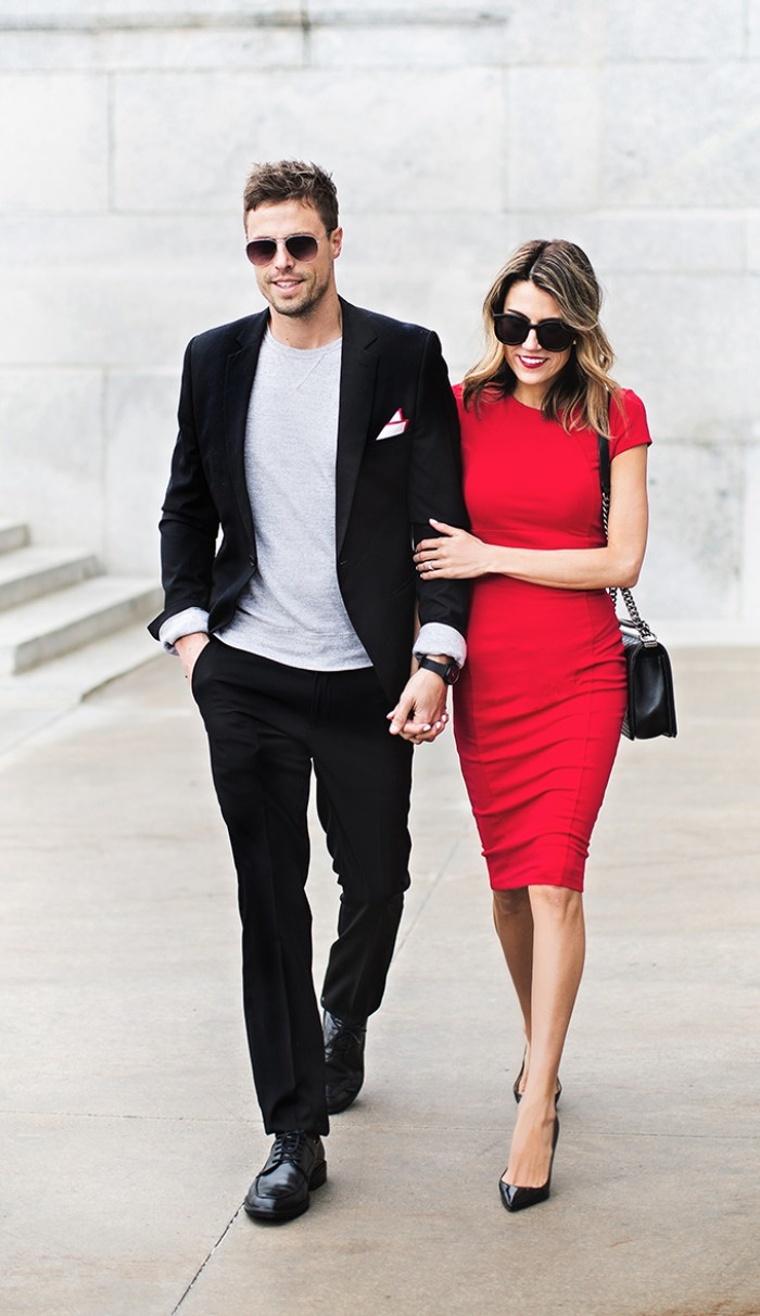 red short-sleeved midi dress, worn by a smiling woman, holding the hand of a man, dressed in a smart black suit, with an off-white t-shirt, black tie optional, black shoes and sunglasses