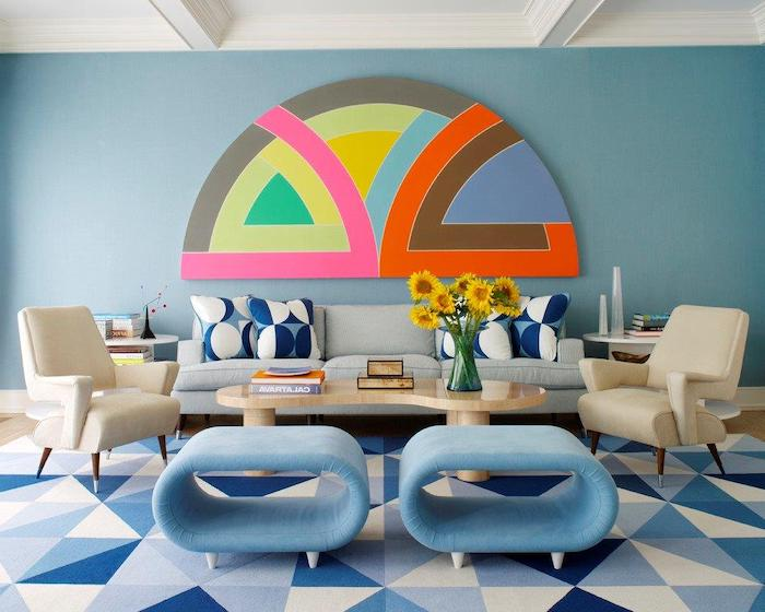 blue wall with a geometrical minimalist painting, blue sofa with blue and white throw pillows, wooden coffee table, white and blue chairs, living room decorating ideas