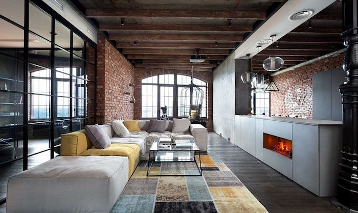 brick walls, dark wooden floor, large white and yellow couch with white and yellow cushions, geometrical blue, grey, yellow and black carpet, fireplace, room ideas