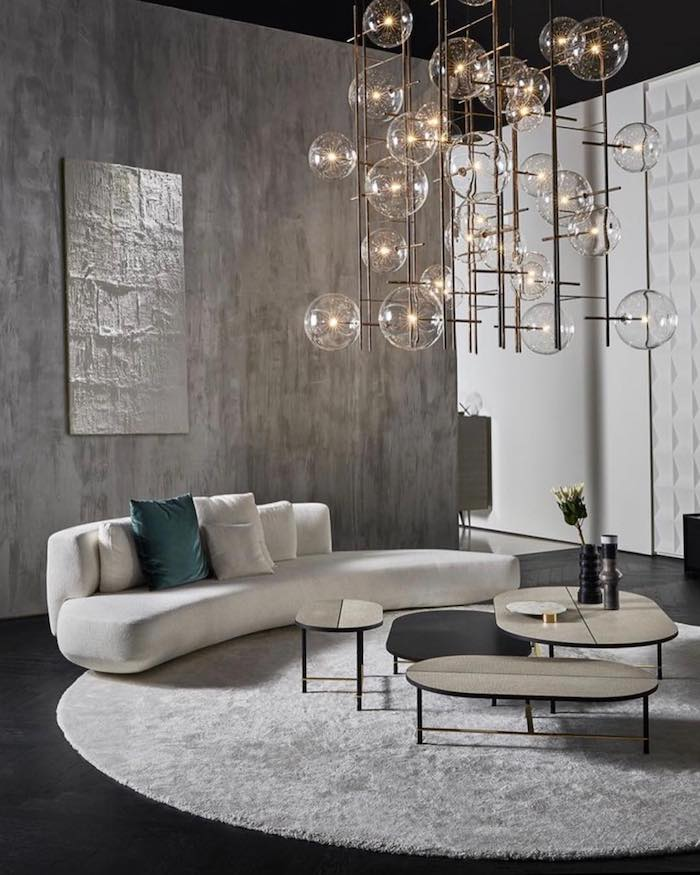 shades of grey walls, black wooden floor, white sofa with white and blue cushions, hanging chandelier, white carpet, small wooden coffee tables, living room furniture ideas