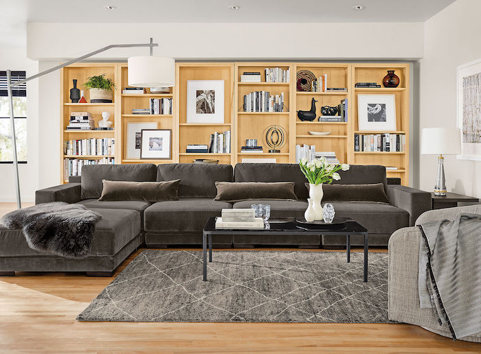 white walls, wooden floor, large wooden bookshelves, dark grey couch, dark grey carpet, small black coffee table, room decor ideas