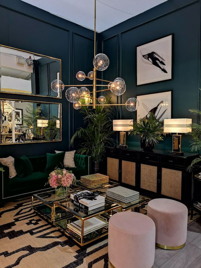 navy walls with mirrors and paintings, dark green sofa with dark green and pink throw pillows, glass and metal coffee table, hanging chandelier, living room decorating ideas