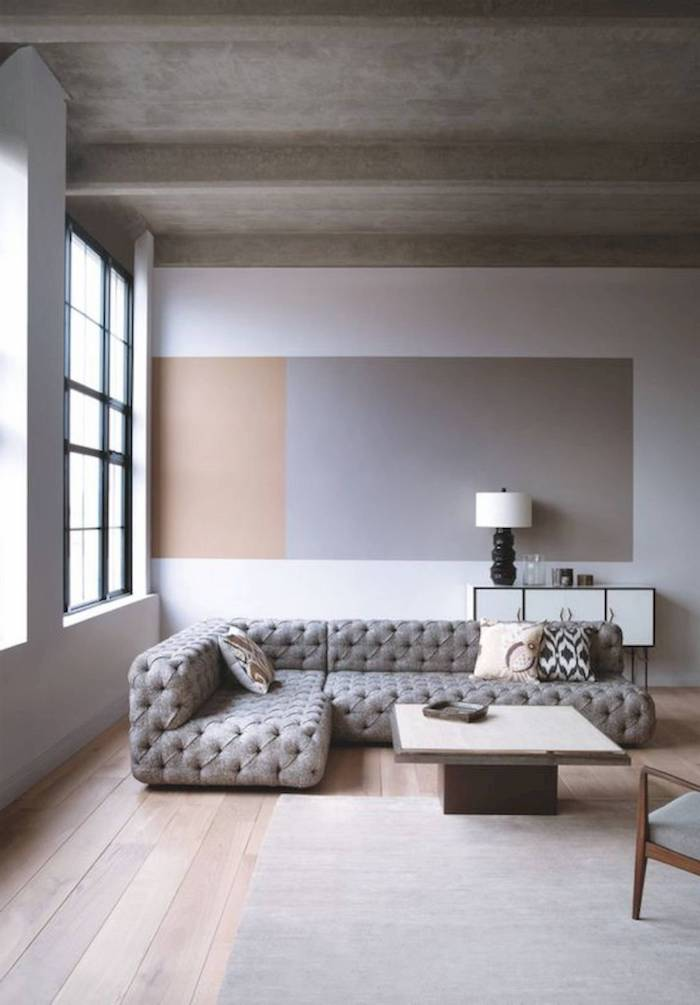 white, grey and beige minimalist wall, wooden floor with grey carpet, grey corner sofa with printed throw pillows, small wooden coffee table, sitting room ideas
