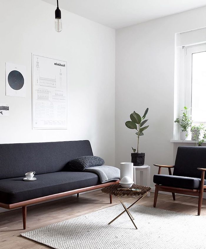 white walls, black sofa and chair, wooden floor with light grey carpet, small round wooden coffee table, sitting room ideas