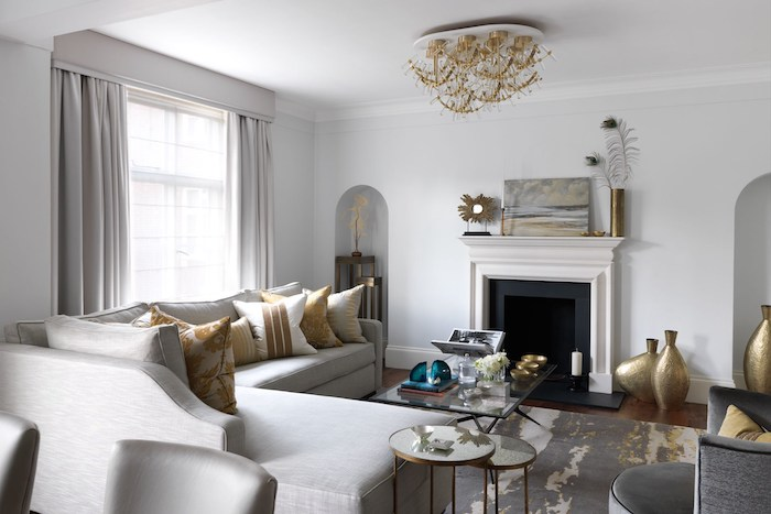 white walls, large white corner sofa with white and gold throw pillows, painting above the fireplace, printed carpet, living room ideas pinterest