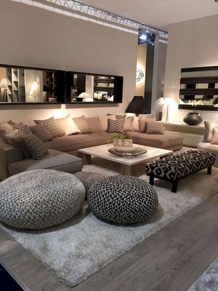 beige walls, large beige sofa with shades of beige throw pillows, wooden floor with grey carpet, large mirror, small living room decorating ideas