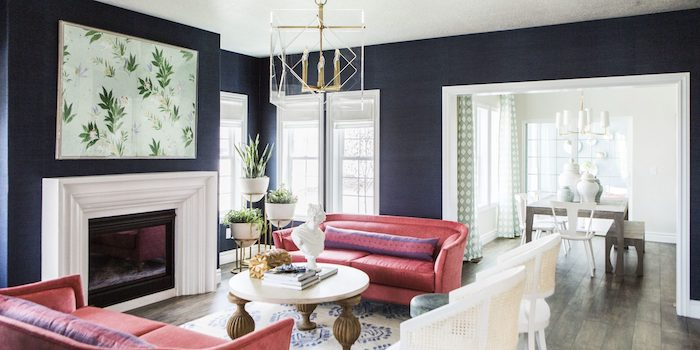 navy blue walls, pink sofas, wooden floor with a printed carpet, painting above the fireplace, modern contemporary design