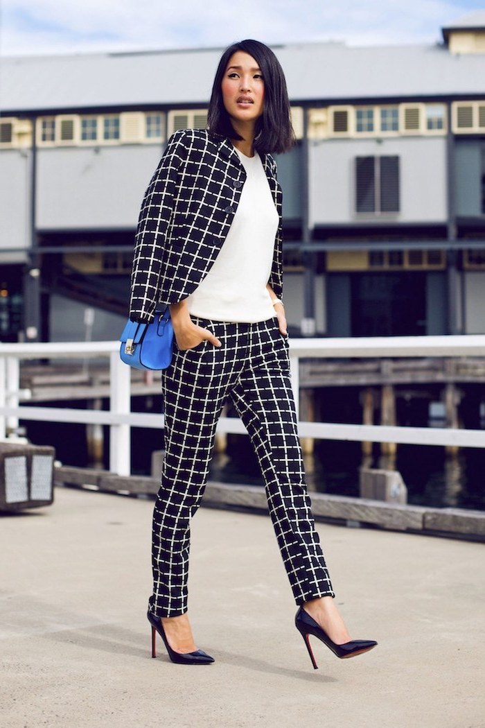 business attire for women, black and white stripe trousers and blazer, white top, black shoes, blue bag