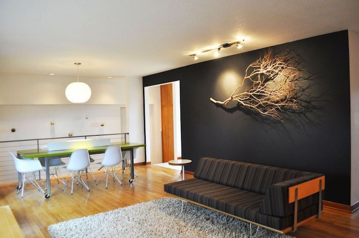 black sofa, black wall with a dried tree branch, wall treatments, white rug, wooden floor