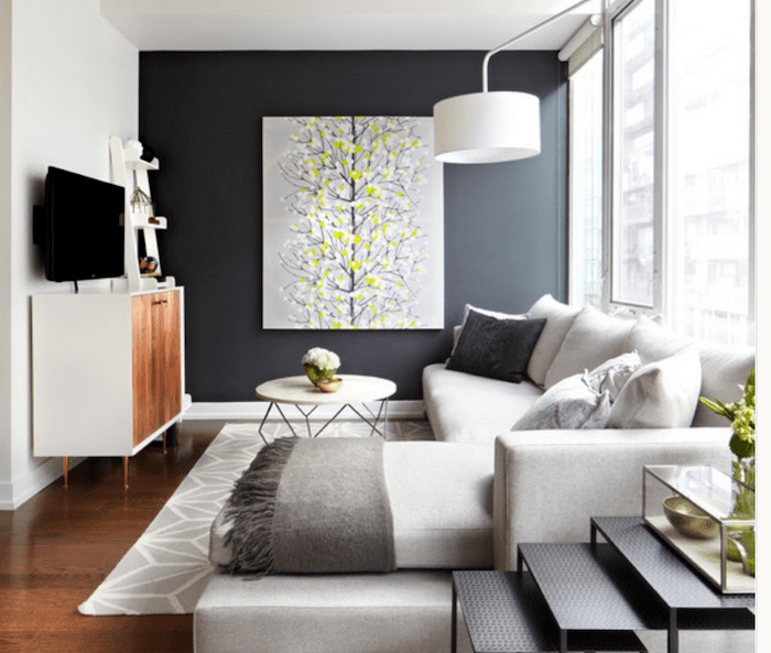 black wall with a grey and yellow painting, white corner sofa, accent wall living room, white and grey rug