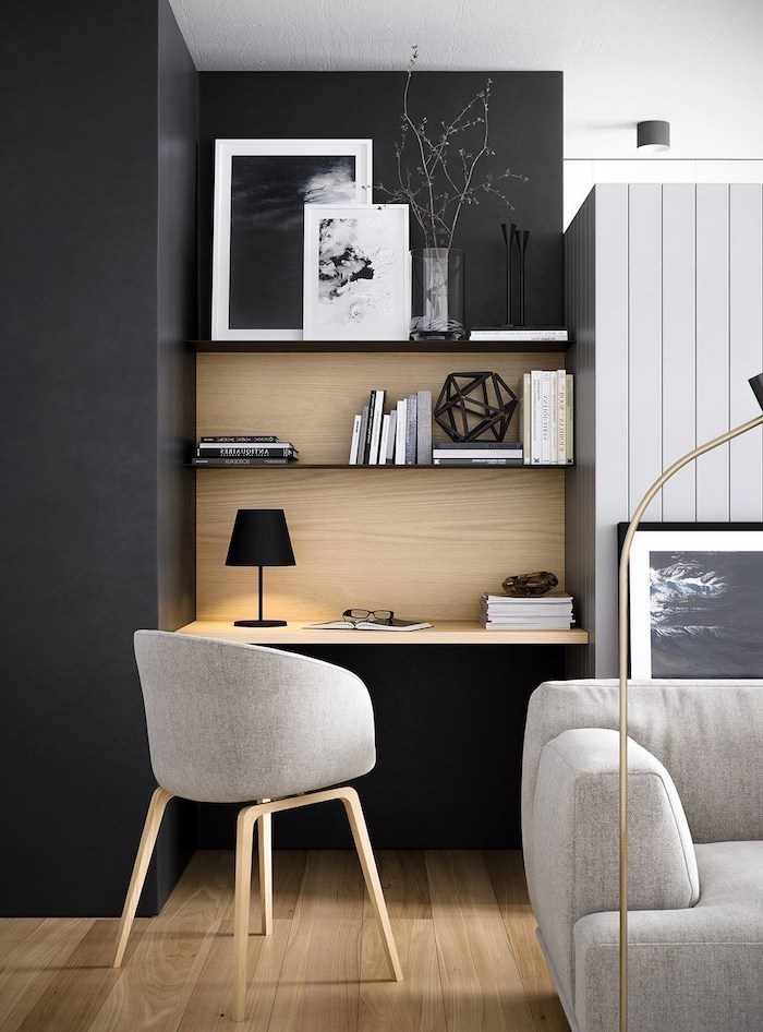 black wall, wooden bookshelves, office design, grey chair, desk lamp