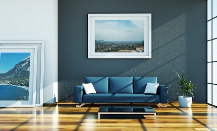 dark blue wall with a framed photo, blue sofa, dining room wall decor, wooden floor