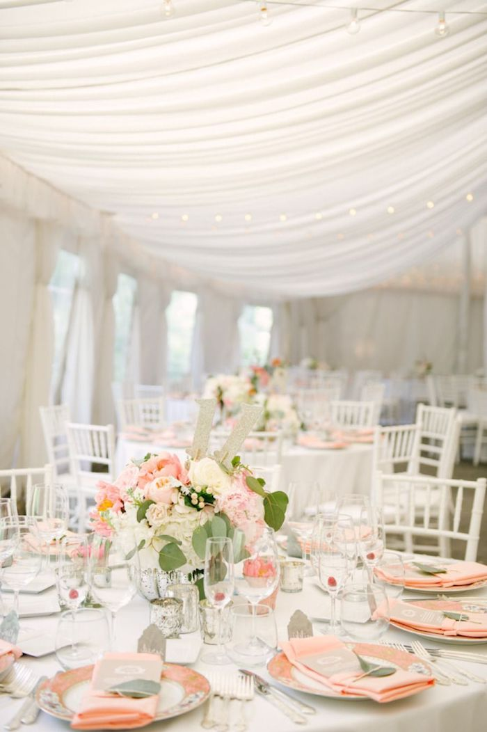 blush and white roses flower bouquets on the tables, blush napkins on the plates, tulle on the ceiling, hanging decorations