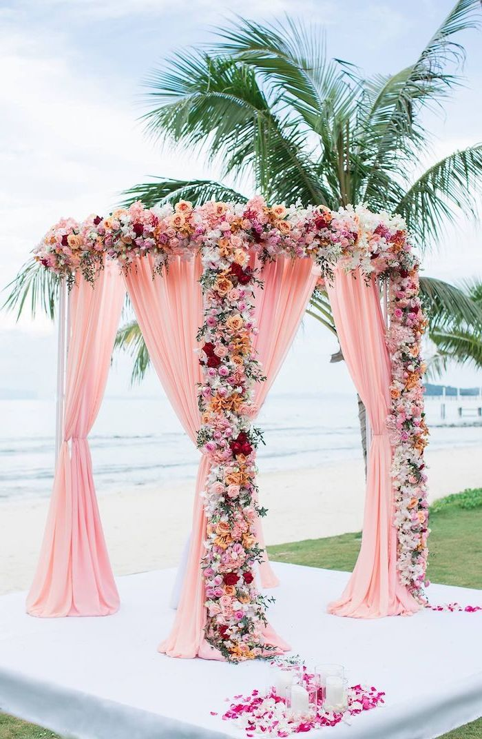blush pink arch, white pink and yellow flowers, palm tree on the beach, wedding decoration ideas