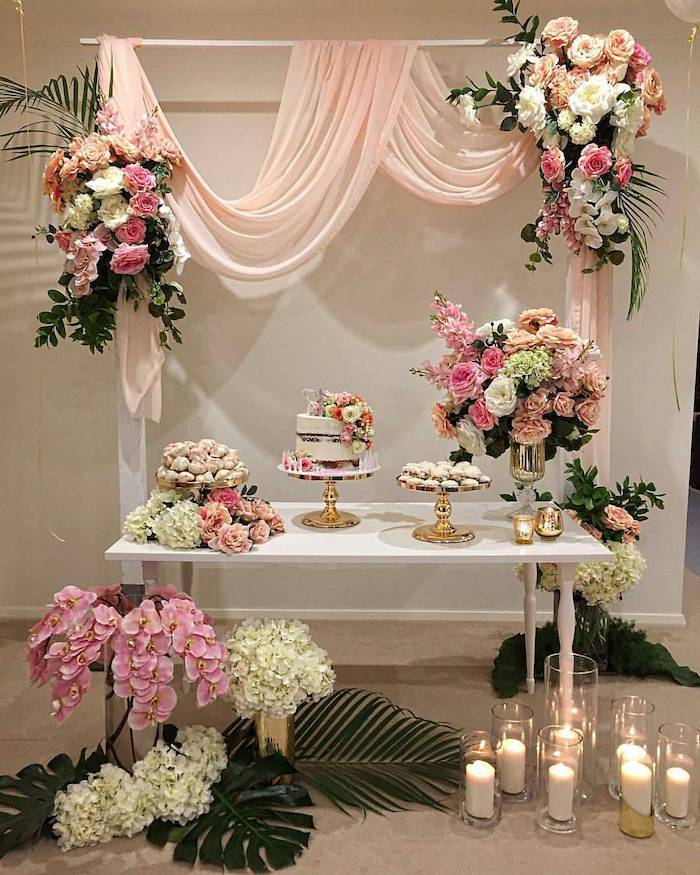 arch with blush tulle and pink white and orange rose flower arrangements, dessert on the table, candles in vases, rustic wedding centrepieces