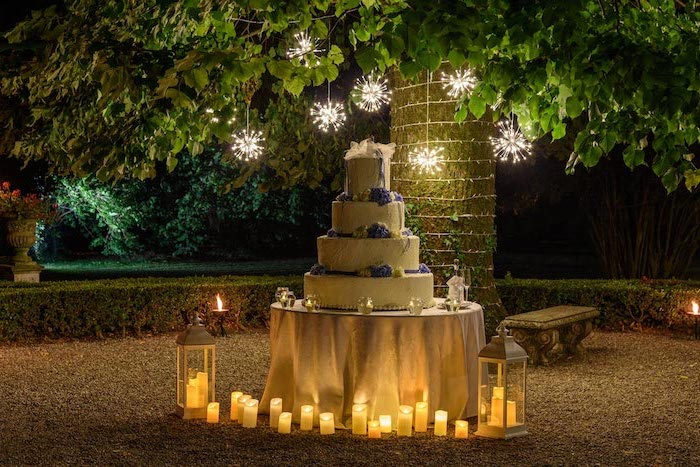 fairy lights on a tree, candles and a lantern, large wedding cake on a table, rustic wedding centrepieces
