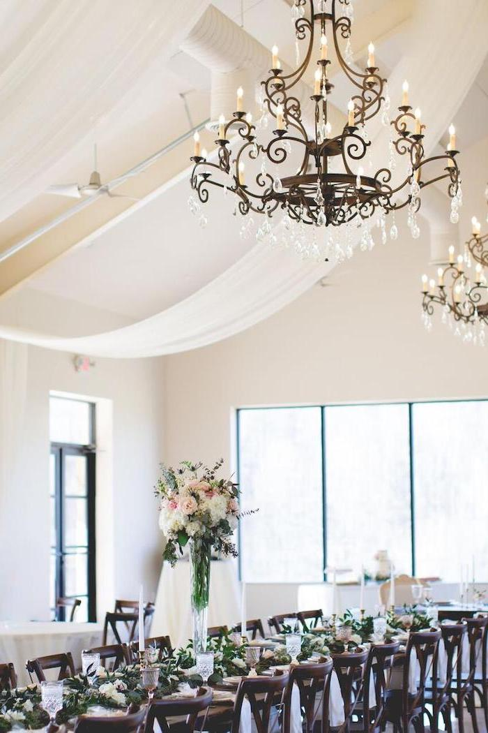 hanging candelabrum chandelier, white yellow and pink roses flower bouquets in high vases on the table, wedding decor