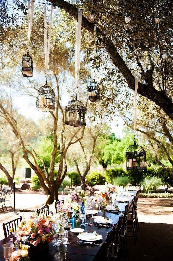hanging bird cages with candles hanging from the tree, pink white and yellow roses bouquets in vases, fall wedding ideas