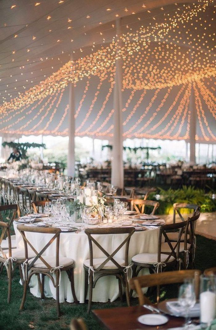hanging fairy lights from the ceiling, candle centrepieces on the tables, wedding reception decorations