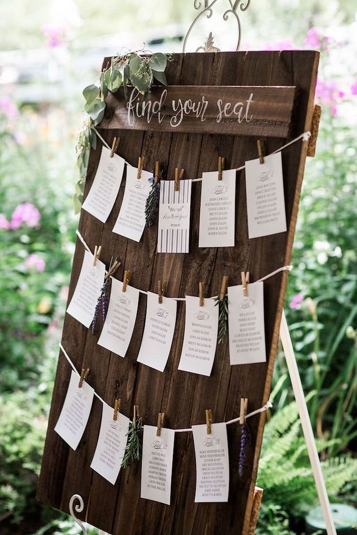 wooden seating chart, papers pinned with pins, greenery in the background, wedding table decoration ideas