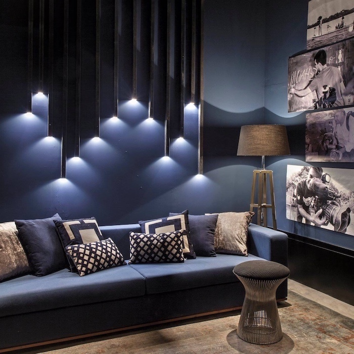 blue walls, geometrical 3d wall installation with lights, accent wall colors, blue sofa, framed photos