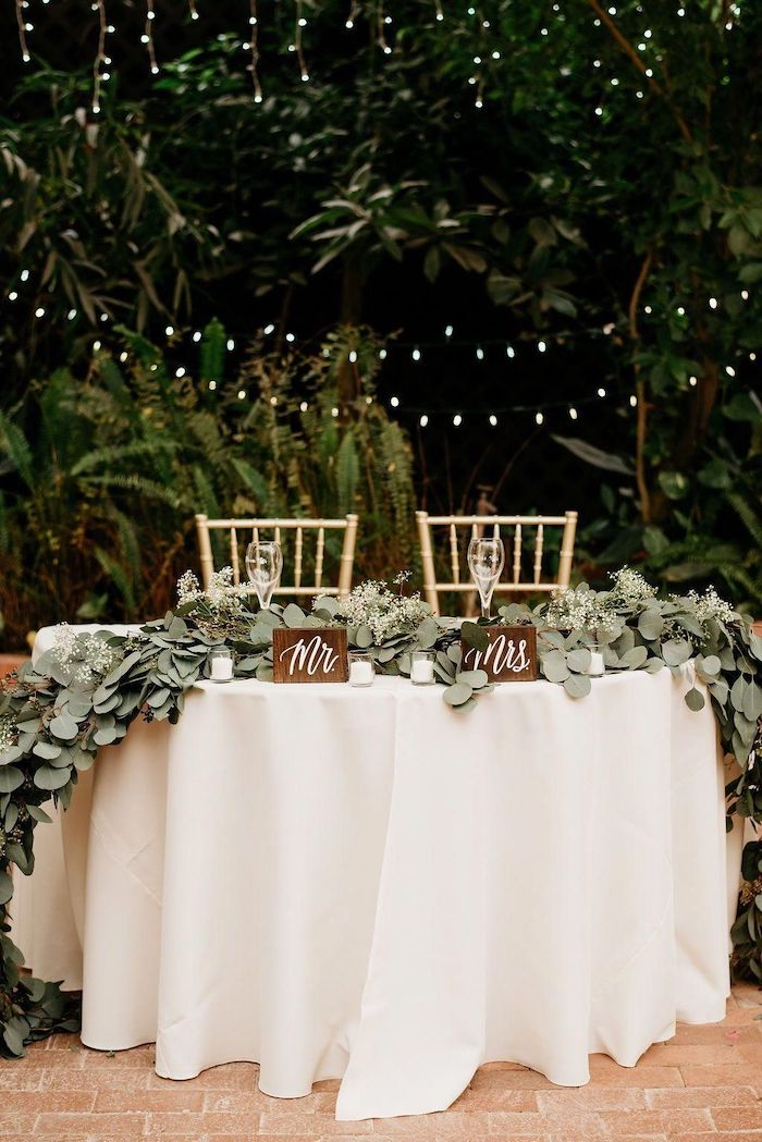 mr and mrs wooden signs, fairy lights and trees in the background, green leaves arrangement on the table, wedding ideas for summer
