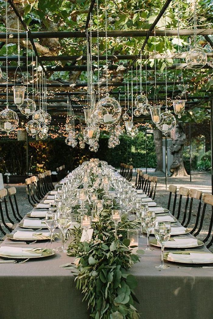 hanging candles from the ceiling, green flower arrangement on the table, dinner sets on the table, wedding reception decorations