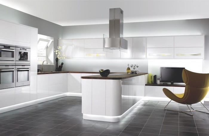 white cabinets and drawers, grey tiled floor, yellow armchair, modern kitchen ideas