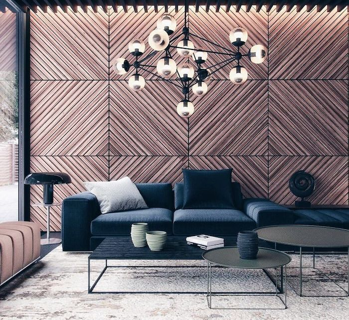 wooden geometrical tiles on the wall, blue velvet sofa, three coffee tables, living room paint ideas