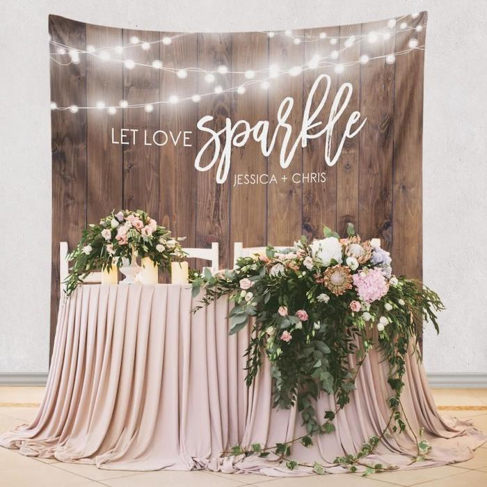 wooden backdrop with fairy lights, large pink and green flower arrangements on the table, flower bouquet in a vase, wedding table settings