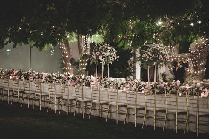 white and pink roses flower arrangement on the table, string lights on the trees, wedding decor