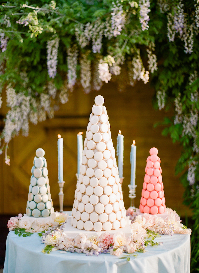 trees made from macaroons, candles on candlesticks, flower arrangements on the table, flowers hanging above, wedding table decorations