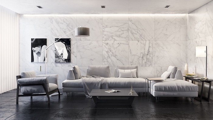 marble tiles on the wall, grey corner sofa and armchair, black floor, wall painting ideas