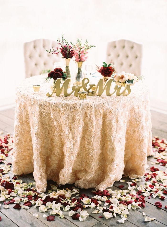 mr and mrs copper sign, pink and red flower bouquets in vases, red and white rose petals on the floor, wedding ideas for summer