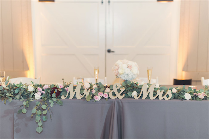 mr and mrs wooden sign, pink and white flower arrangement on the table, white roses bouquet in a vase, wedding table settings