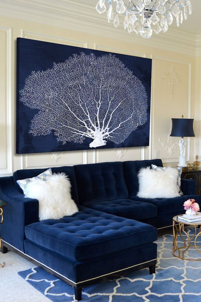 white patterned framed wall, navy blue velvet sofa, blue and white tree painting, feature wall, blue rug