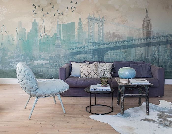 new york skyline wallpaper, purple velvet sofa, accent wall, blue armchair, wooden floor