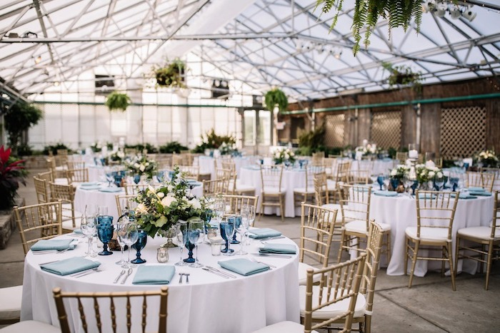 blue napkins and glasses, white roses flower bouquets on the tables, wedding reception decorations