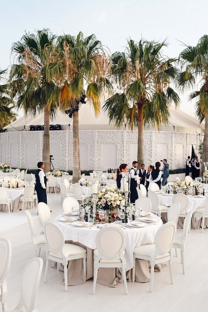 big palm trees, white round tables, yellow and pink roses bouquets, wedding ceremony decorations