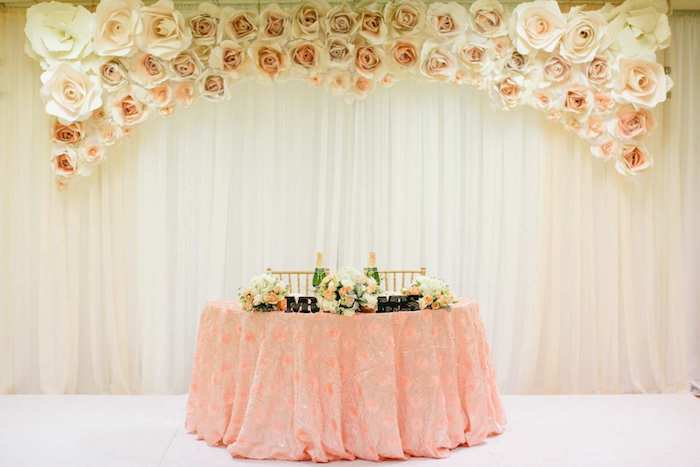 mr and mrs metal sign, white and pink paper roses, flower bouquets in vases on the table, rustic wedding centrepieces