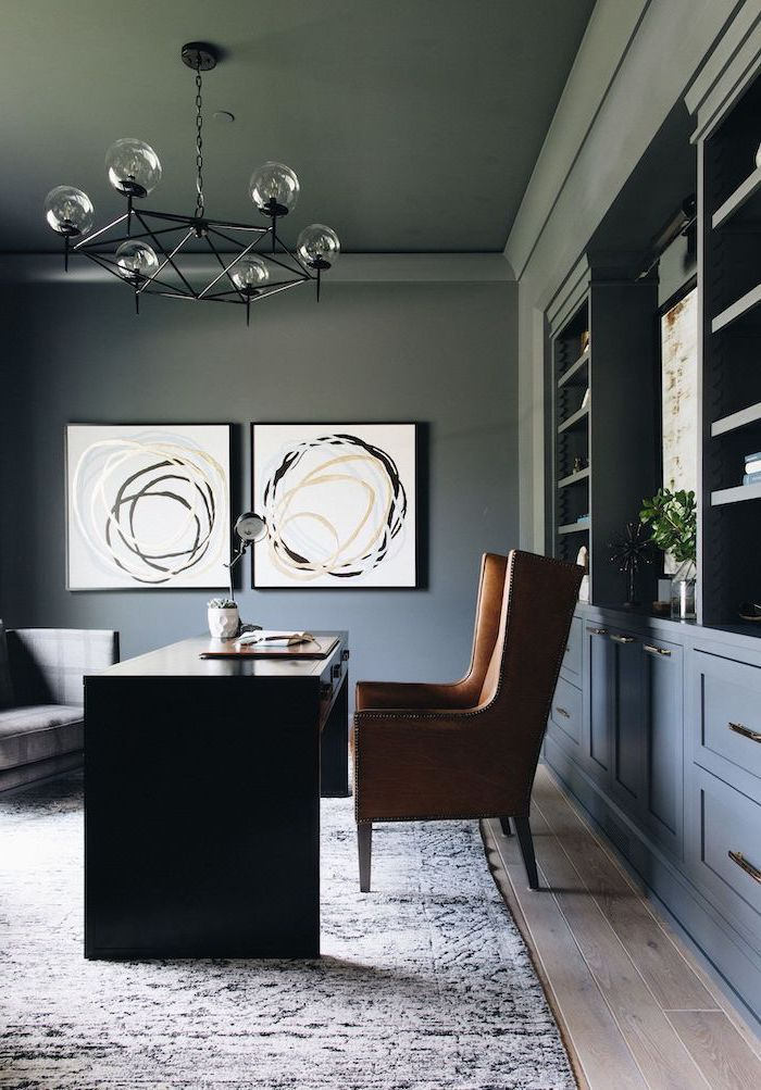 grey walls and bookcase with shelves and cupboards, large brown armchair, black desk, office design ideas