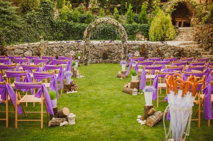 arch made of pink flowers, wooden chairs with purple bows, wood along the aisle, rustic wedding ideas