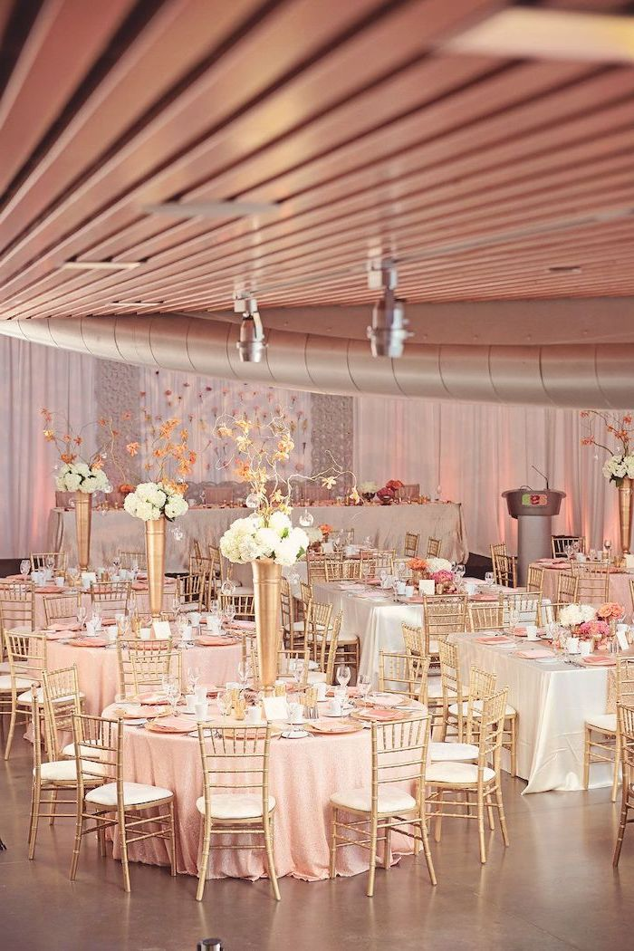 rose gold theme, white flower bouquets in high vases on the tables, ceiling hanging decor