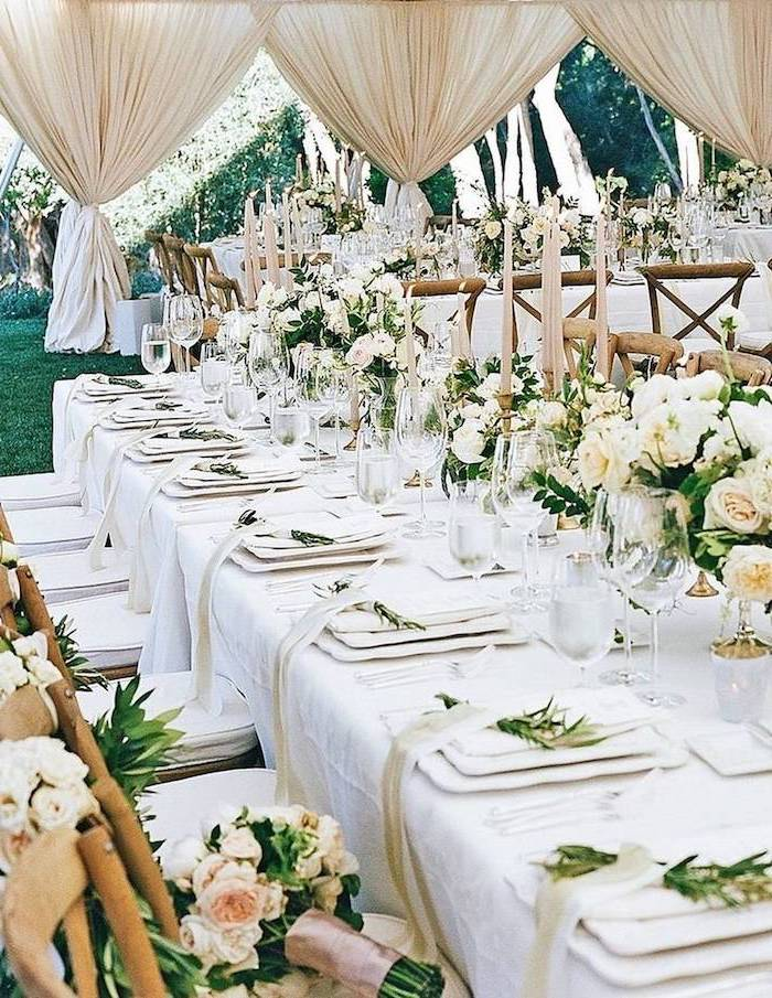 white roses bouquets in vases on the table and on the chairs, candles in candelabrums, ceiling hanging decor