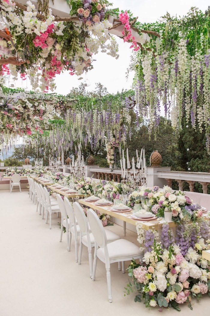 hanging white pink and purple flower arrangements from the ceiling, candles in candelabrums on the table, ceiling hanging decor