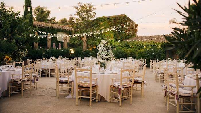 hanging string lights, white flower arrangements on the tables in vases, ceiling hanging decor